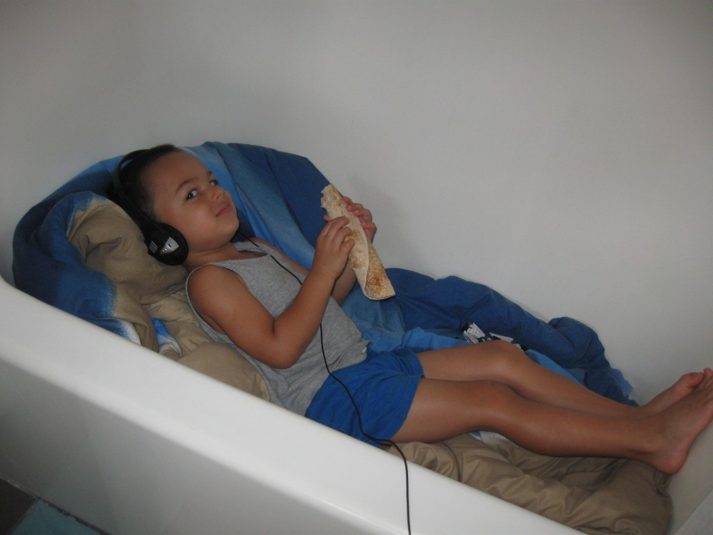 Listening to stories in a bathtub cubby while mom and dad write music